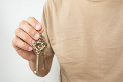 Gold key chain with key in hand Royalty Free Stock Photos