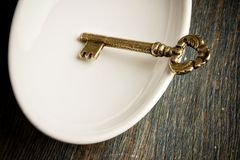 Gold Key in Dish. Gold key in a white dish Stock Photography