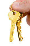Gold key in fingers Royalty Free Stock Photography