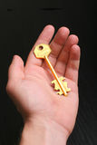 Gold key in hand. Man holding the gold key royalty free stock photography