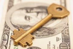 Gold key on hundred dollar bill. Isolated Stock Photos