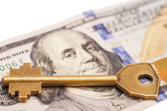 Gold key on hundred dollar bill Stock Photo