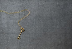Gold key lying on the leather pad. Gold key with chain lying on the leather pad Royalty Free Stock Photography