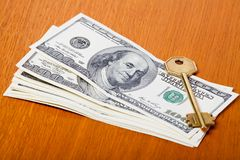 Gold key and money. Stacks of 100 dollar bills with gold key Stock Photo