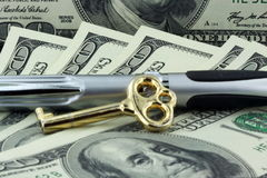 Gold key and pen on hundred Dollars  Royalty Free Stock Images