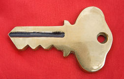 Gold key on red.  Royalty Free Stock Image