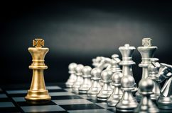 Gold King in chess game face with the another silver team on bla royalty free stock photography