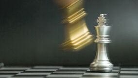 Gold king chess piece knock and win over silver team on black background Concept for company strategy, business victory