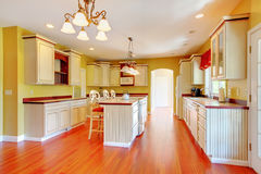 Gold kitchen with white antique cabinets. Gold kitchen with white antique cabinets and cherry hardwood Stock Photo