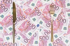 Knife and fork on the money. Gold knife and fork on a background of paper money with a face value of five hundred euro stock photography