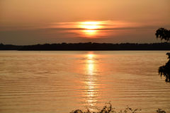 Gold lake sunset with the sun Partially hidden. Gold lake sunset sun partially hidden for clouds and nice reflected on the golden water of the lake background or Stock Image