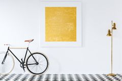 Gold lamp and black bike on checkerboard floor in anteroom inter. Ior with painting on the wall royalty free stock photography