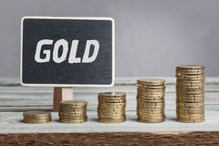Gold language on sign. Gold, white chalk type on black board, Euro money coin stacks of growth on wood table stock images