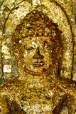Gold leaf covered Buddha face. Golden Buddha face a local folk art craftsmanship with close adherence to the gold leaf shelters and happiness enshrined in Stock Image