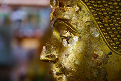 Gold leaf on the eyes of Buddha statue Royalty Free Stock Images