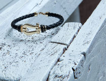 Gold and leather bracelet. Beautiful bracelet made of gold and leather on a nice textured background stock photo