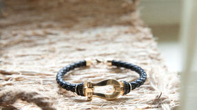 Gold and leather bracelet. Beautiful bracelet made of gold and leather on a nice textured background Stock Photos