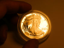 Gold liberty. One dollar coin in hand - reflex gold stock photography