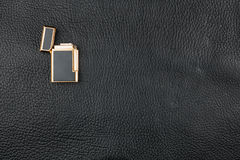Gold Lighter lies on natural leather Stock Photo
