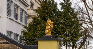 Gold lion on a pedestal in front of the gate to the estate, gold Stock Photo