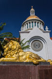 Gold lion statue  in front of  church. Gold lion statue  is in front of  church, blue  isolated Royalty Free Stock Images