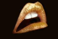 Gold lips. Shining on black isolated background Stock Photo