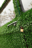 A gold lock on an old green grass decorated car. Stock Photos