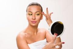 Gold make up. Brown sleek hair beautiful woman looking at mirror.  Stock Photos
