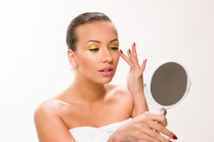 Gold make up. Brown sleek hair beautiful woman looking at mirror Royalty Free Stock Photo