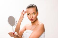 Gold make up. Brown sleek hair beautiful woman looking at mirror Royalty Free Stock Photos