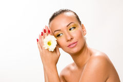 Gold make up. Brown sleek hair beautiful woman with white flower in hands close to face looking down. Stock Photography