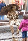 Gold man show a little girl Stock Photography