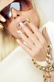 Gold manicure. Gold manicure with rhinestones, chain and textured with snake on girl blonde with glasses Royalty Free Stock Photos