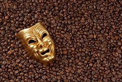Gold mask on coffee beans background. Stock Photos