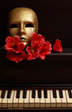 Gold mask on piano. Gold mask and red flower on a piano Stock Image