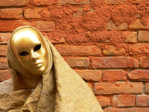 Gold mask and red wall. Closeup of a very simple gold mask on a red wall background at venice carnival stock photos