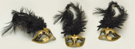 Gold masks. With black feathers in three different views