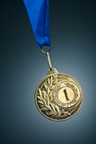Gold medal. Artistic gold medal on blue background Royalty Free Stock Photo
