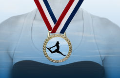 Gold Medal. With red white blue ribbon against clouded background/woman's chest.  Silhouette of woman leaping in medal Stock Photo