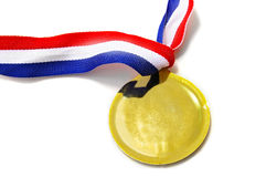 Gold medal. A blank gold medal with ribbon, on white Royalty Free Stock Photo