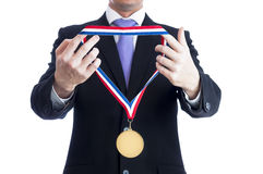 Gold medal. Cropped torso of man wearing black suit and awarding blank sports gold medal Royalty Free Stock Photography