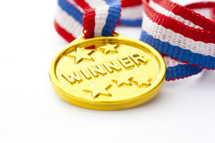 Gold medal. Closeup of gold medal and ribbon on white background Royalty Free Stock Photography