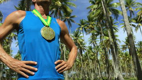Gold Medal Athlete Standing with Palm Trees Brazil. First place athlete wearing gold medal standing outdoors with hands on hips in grove of tropical palm trees stock footage