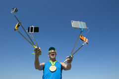 Gold Medal Athlete Taking Selfies with Selfie Sticks. Gold medal athlete makes a face for his many gadgets on selfie sticks as he poses for a picture Royalty Free Stock Photos