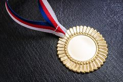 Gold medal - award for a winner on black background Stock Photos