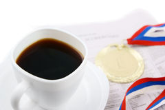 Gold medal and coffee cup on newspaper isolated Royalty Free Stock Photos