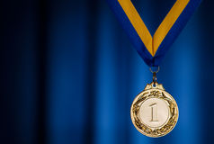 Gold medal on a dark blue background. Gold medal in the foreground on yellow blue ribbon Royalty Free Stock Image