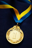 Gold medal on a dark blue background. Gold medal in the foreground on yellow blue ribbon Royalty Free Stock Photo