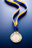 Gold medal on a dark blue background. Gold medal in the foreground on yellow blue ribbon Royalty Free Stock Images