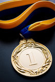 Gold medal on a dark blue background. Gold medal in the foreground on yellow blue ribbon Stock Photography